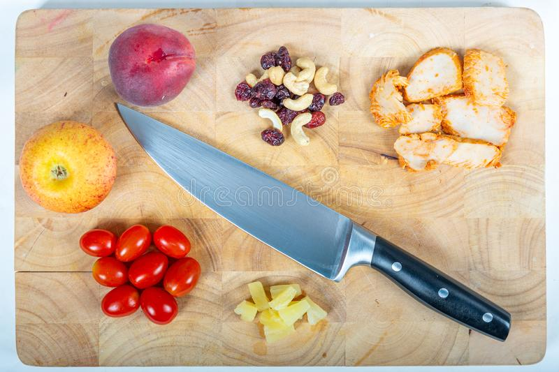 Top view of an apple, a peach, tomatoes, pieces of pineapple, chicken, raisins and peanuts with a knife stock photo