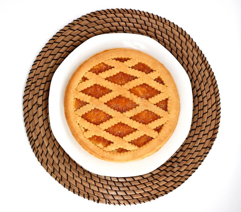 Top view of an apricot jam tart on plate and round table mat. royalty free stock photo
