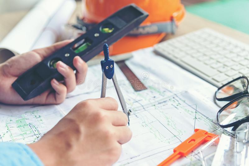 Top View Architect working on blueprint. Architects workplace.  Engineer tools and safety control,  blueprints, ruler, orange helm stock image