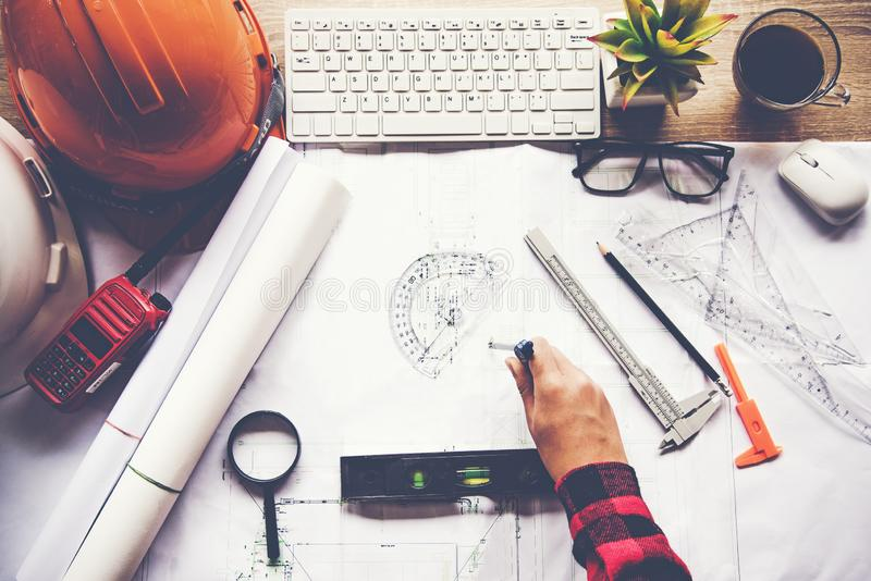 Top View Architect working on blueprint. Architects workplace. Engineer tools and safety control, blueprints, ruler, radio, laptop. And divider compass stock photo