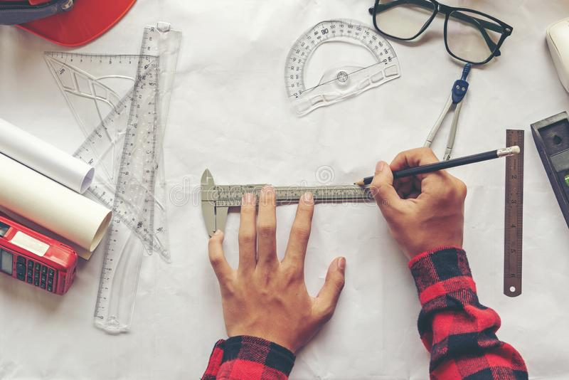 Top View Architect working on blueprint. Architects workplace. Engineer tools and safety control, blueprints, ruler, radio stock photo