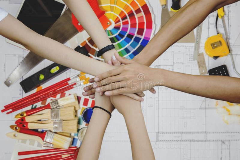 Top view of architects hands group of young creative working wit. H work tools, color swatches and painting rollers at bottom stock image
