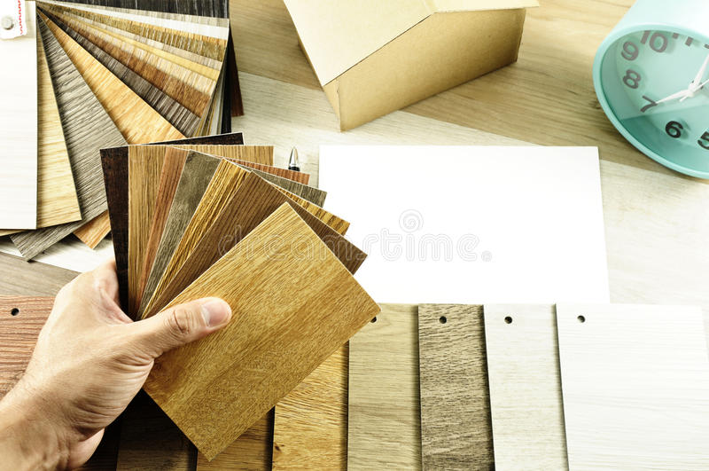 Top view of Architects & Interior designers hands design to choose wood floor materials on table in workplace in the morning. stock image