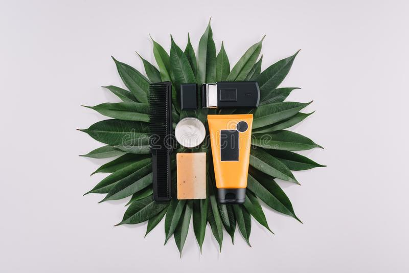 top view of arranged barber tools on green leaves royalty free stock photos