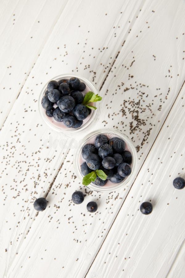 top view of arranged chia puddings with fresh blueberries and mint on white wooden surface royalty free stock photography