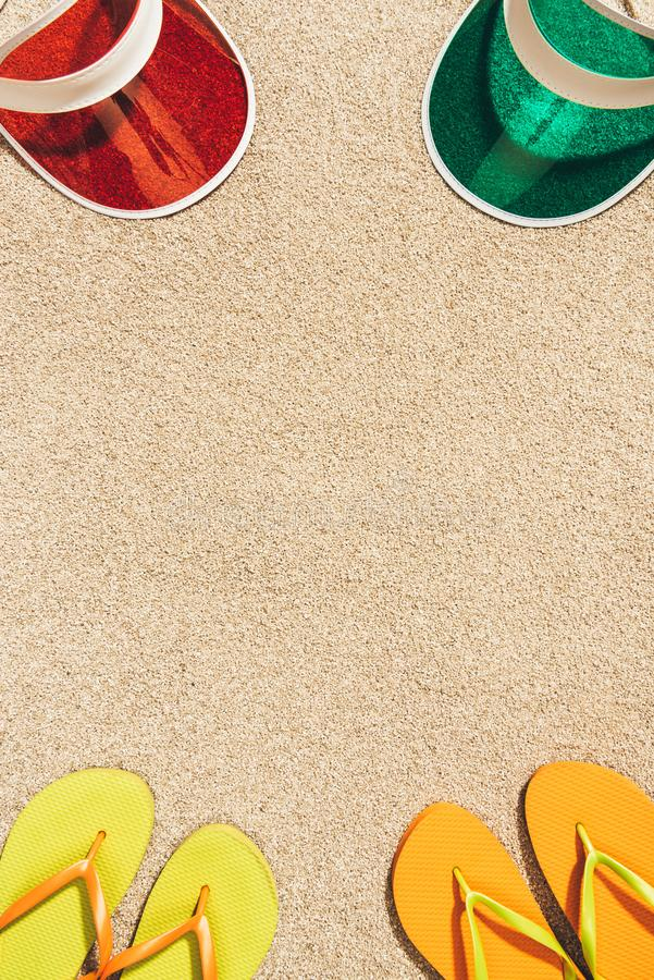 Top view of arranged colorful caps and flip flops. On sand stock photography