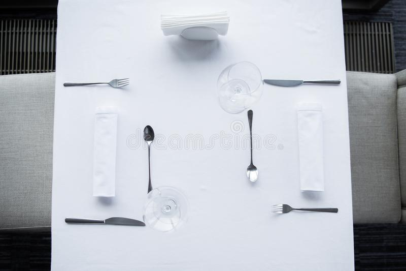 top view of arranged cutlery and wineglasses on table with white tablecloth stock photography