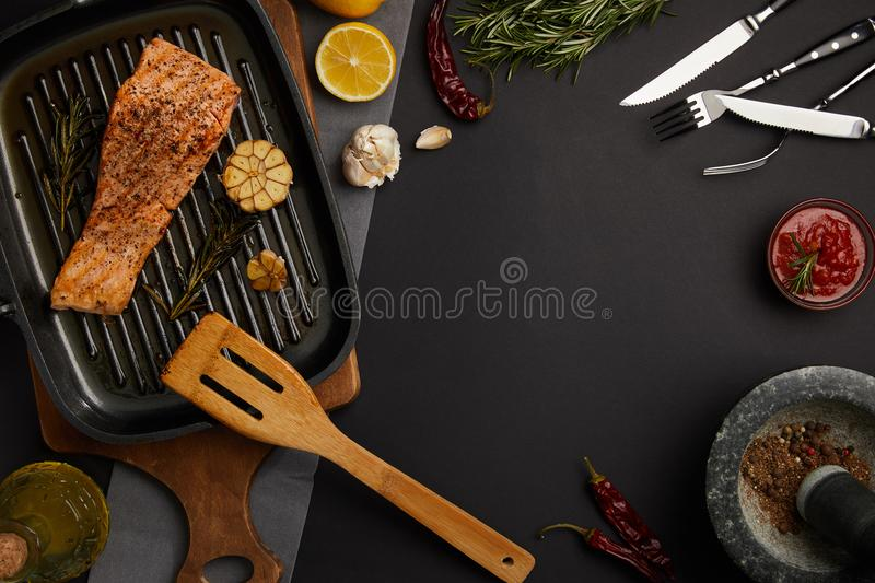 Top view of arranged grilled salmon steak on wooden cutting board, ingredients, sauce and cutlery on black tabletop royalty free stock photography