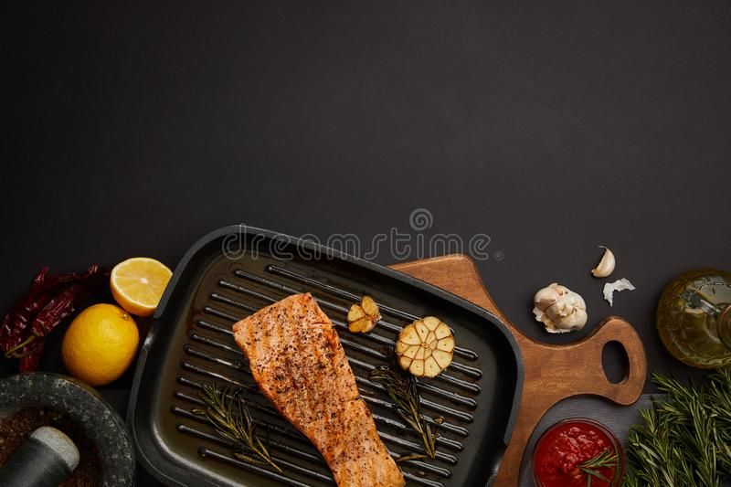 Top view of arranged grilled salmon steak on wooden cutting board, sauce, ingredients and cutlery on black tabletop stock image