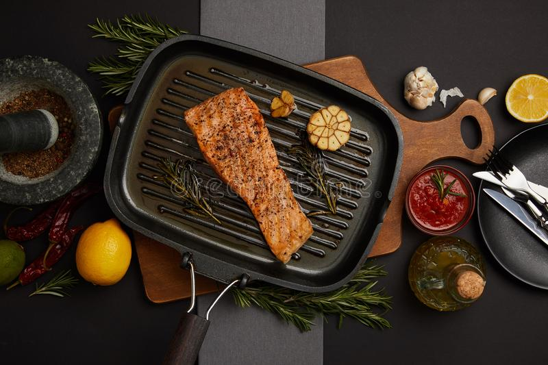 Top view of arranged grilled salmon steak on wooden cutting board, sauce, ingredients and cutlery on black tabletop stock photography