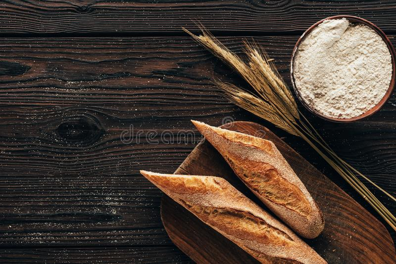 Top view of arranged pieces of french baguette on cutting board, wheat and flour in bowl. On wooden surface royalty free stock photography