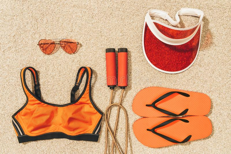 Top view of arranged skipping rope, sportswear, sunglasses, cap and flip flops. On sand stock images
