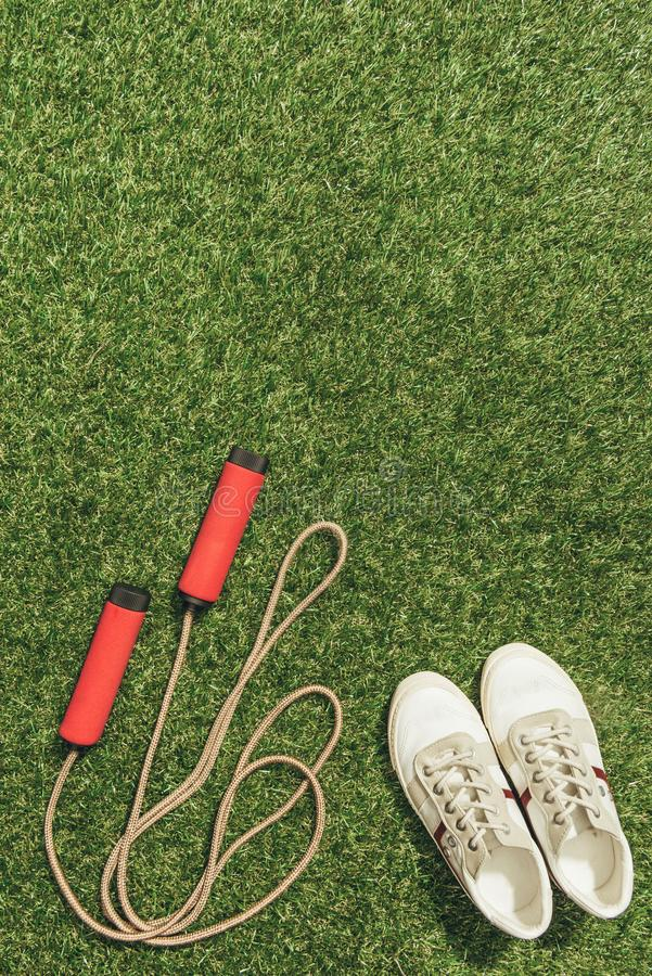 Top view of arranged sneakers and skipping rope. On green grass royalty free stock images