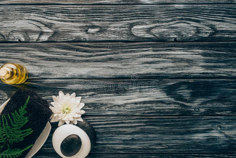Top view of arranged spa and massage accessories with towel, pebbles, essential oil and chrysanthemum flower. On wooden background stock images