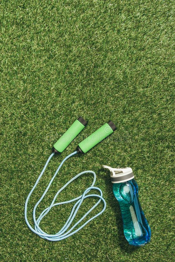 Top view of arranged water bottle and skipping rope. On green grass royalty free stock image