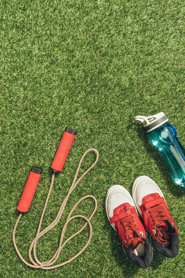 Top view of arranged water bottle, skipping rope and sneakers. On green grass royalty free stock photo