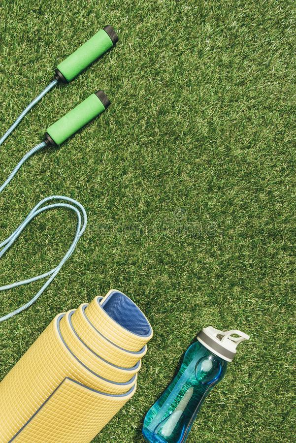 Top view of arranged yellow mat, skipping rope and water bottle. On green grass stock photo