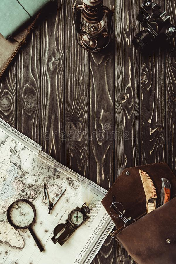 Top view of arrangement with map, magnifying glass, bag, compass and retro photo camera on dark. Wooden surface stock photo