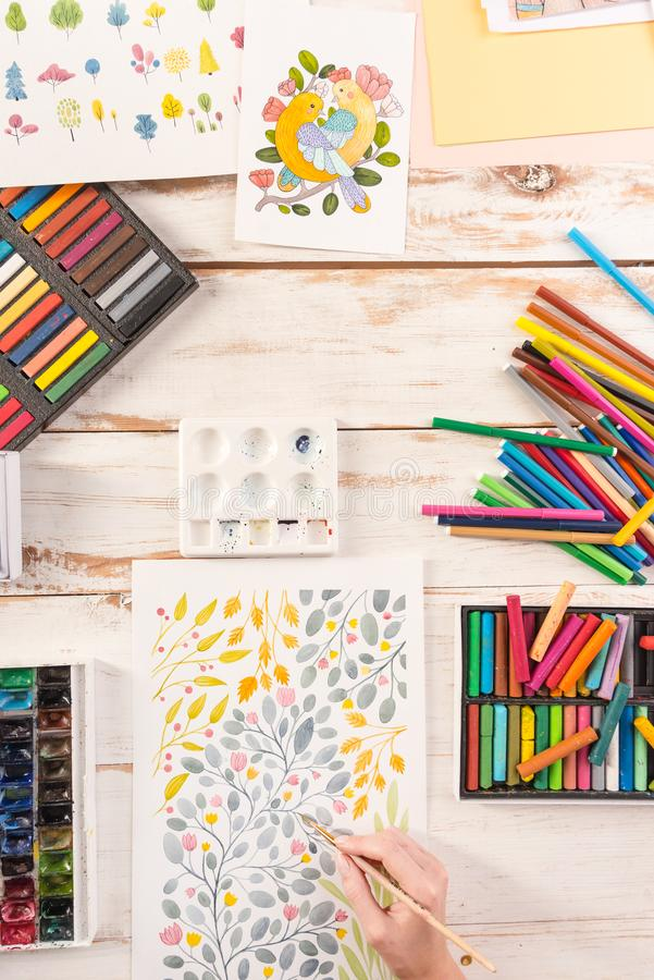 Top view of artist drawing flowers design at workplace. Top view of artist drawing colorful flowers design at workplace. Artist equipment: acrylic paint, pastele royalty free stock photos
