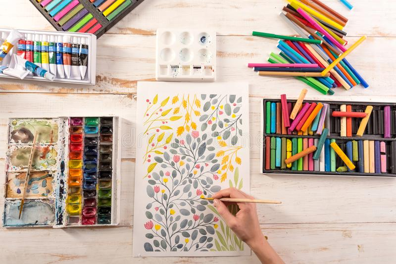 Top view of artist drawing flowers design at workplace. Top view of artist drawing colorful flowers design at workplace. Artist equipment: acrylic paint, pastele stock photos