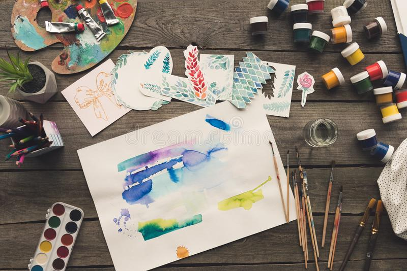 Top view of artist sketches drawn with watercolor paints on a. Wooden table stock photos