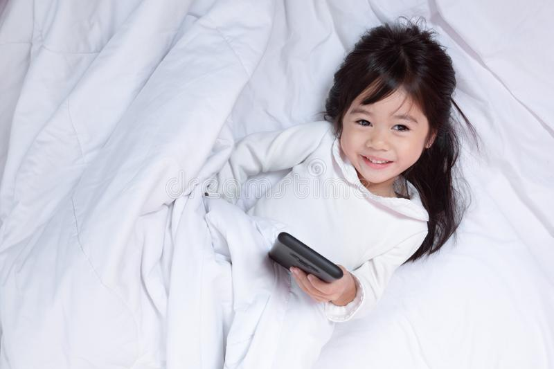 Top view of Asia little kid having fun playing smartphone stock images