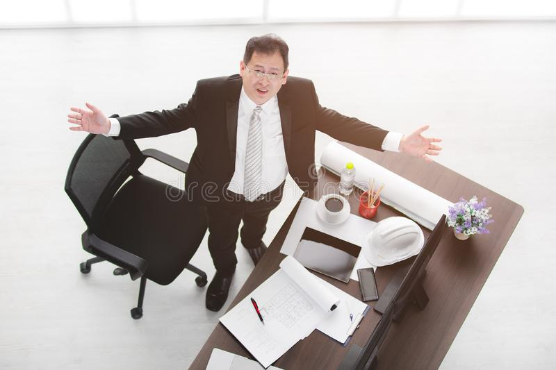 Business man at office. Top view of Asian business man in black suit, wearing glasses, standing between table and chair, look upwards, arms wide open with royalty free stock image