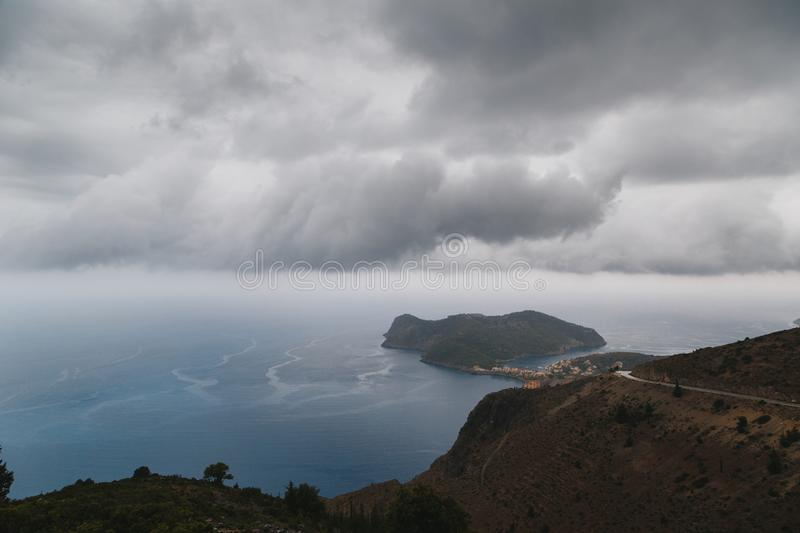 A top view at Asos village and Assos peninsula from a road during the bad weather conditions, thunderstorm and rain stock photos