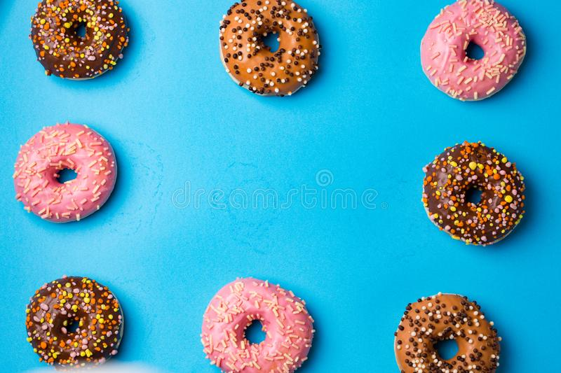 Top view of assorted donuts on blue concrete background with copy space. Colorful donuts background. royalty free stock photo