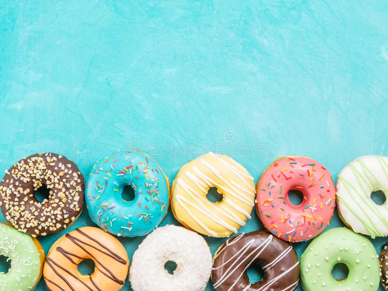 Donuts on blue background , copy space, top view. Top view of assorted donuts on blue concrete background with copy space. Colorful donuts background. Various stock images