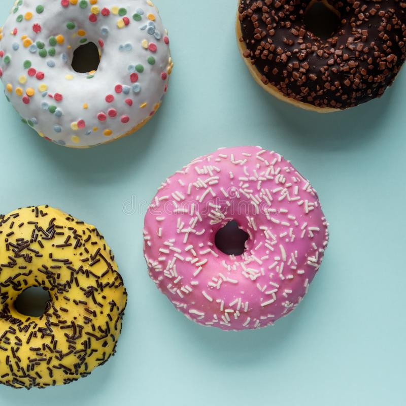 Top view of assorted donuts with chocolate frosted, pink glazed and sprinkles on a blue background. royalty free stock photography