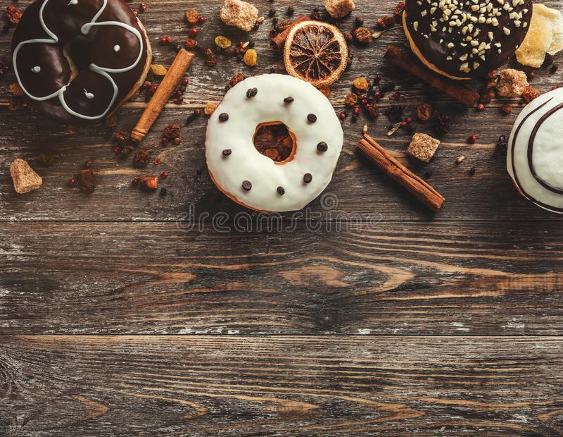 Top view of assorted donuts on wooden background with copy space stock photography
