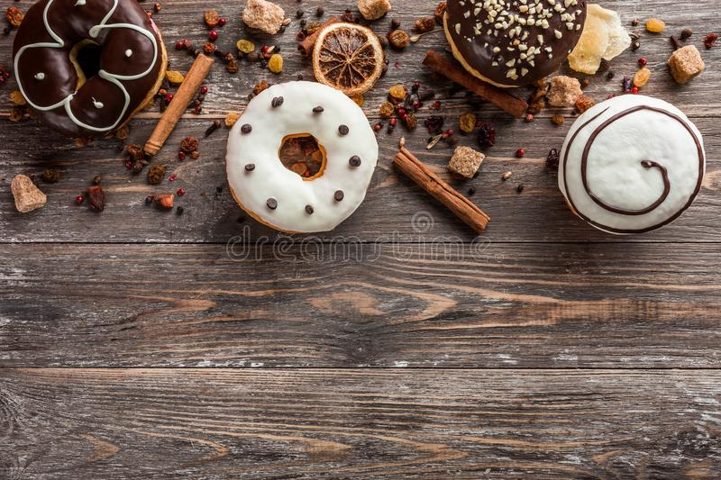 Top view of assorted donuts on wooden background with copy space stock images