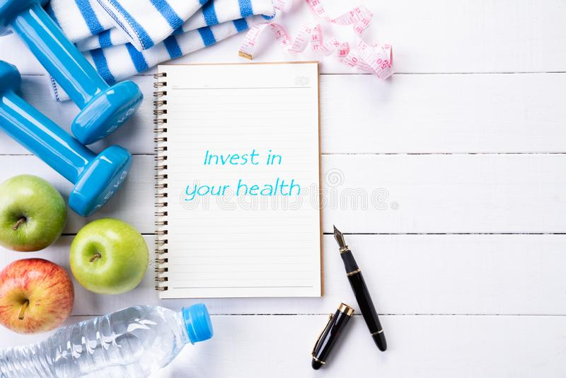 Top view of athlete`s equipment blue dumbbell, sport water bottles, towel and note book with Invest in your health text on white stock photos