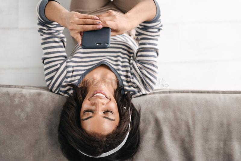 Top view of an attractive young afro american woman. Sitting at a couch at home, using mobile phone, wearing headphones royalty free stock image