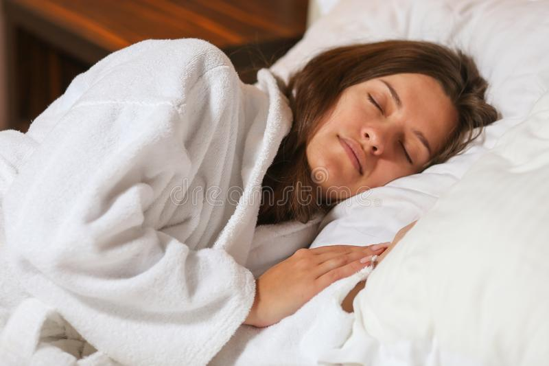 Top view of attractive young woman sleeping well in bed hugging soft white pillow. Teenage girl resting, good night sleep concept. Lady enjoys fresh soft royalty free stock photography