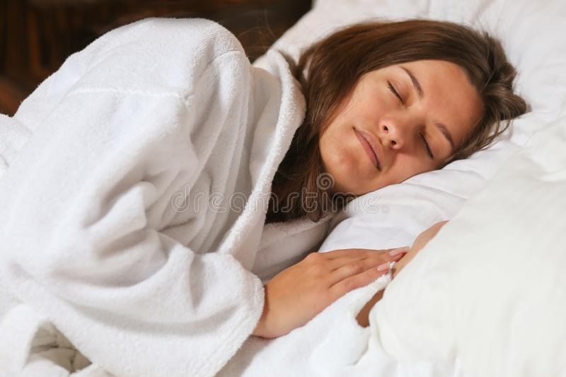 Top view of attractive young woman sleeping well in bed hugging soft white pillow. Teenage girl resting, good night sleep concept. Lady enjoys fresh soft stock photo