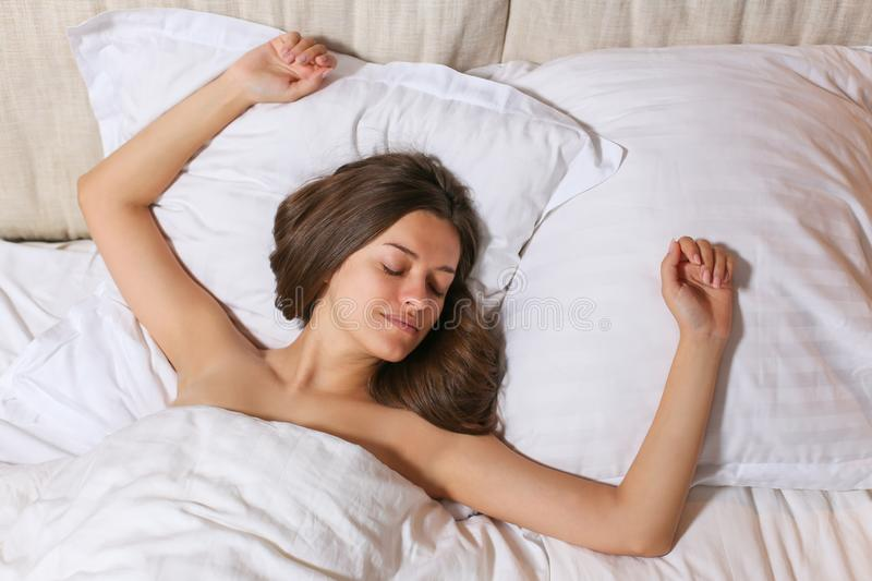 Top view of attractive young woman sleeping well in bed hugging soft white pillow. Teenage girl resting, good night sleep concept. Lady enjoys fresh soft stock image