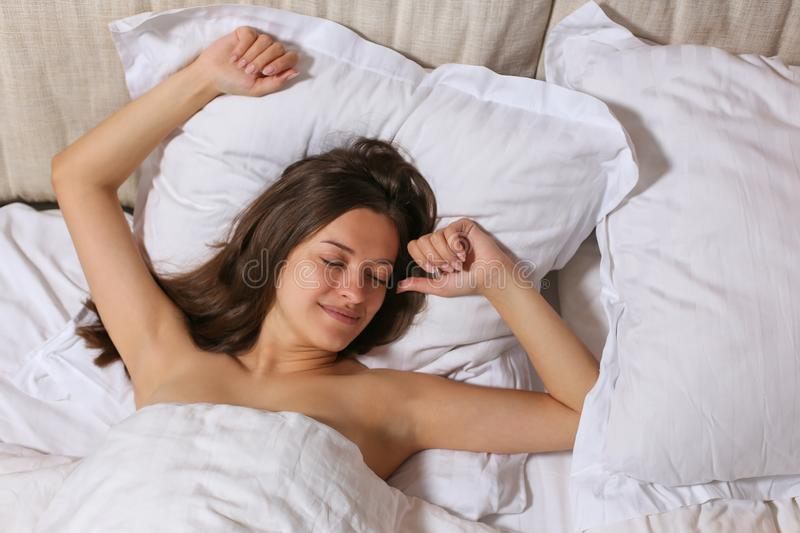 Top view of attractive young woman sleeping well in bed hugging soft white pillow. Teenage girl resting, good night sleep concept. royalty free stock photography