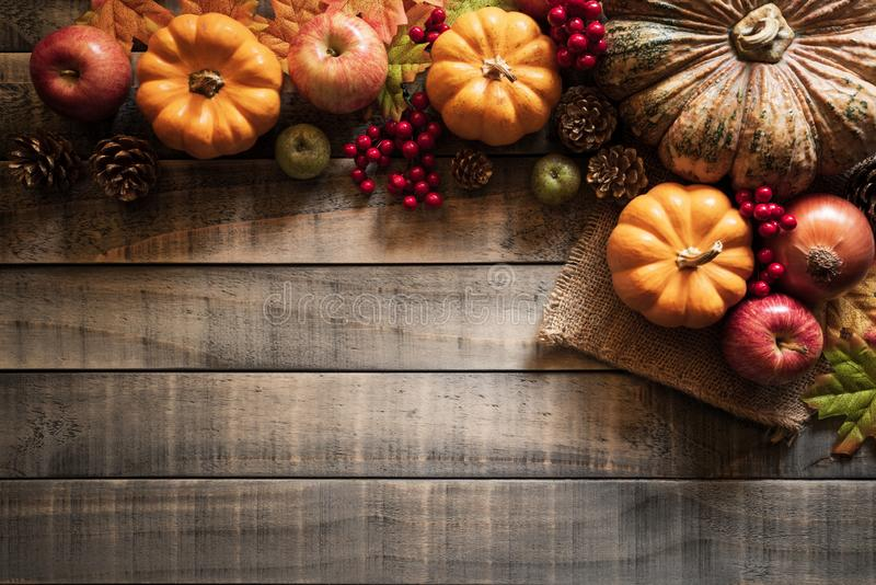 Top view of Autumn maple leaves with Pumpkin and red berries on old wooden backgound. stock image