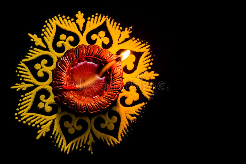 Top view of awesome glowing diya and rangoli on black backgorund with copy sapce. festival of light royalty free stock photography