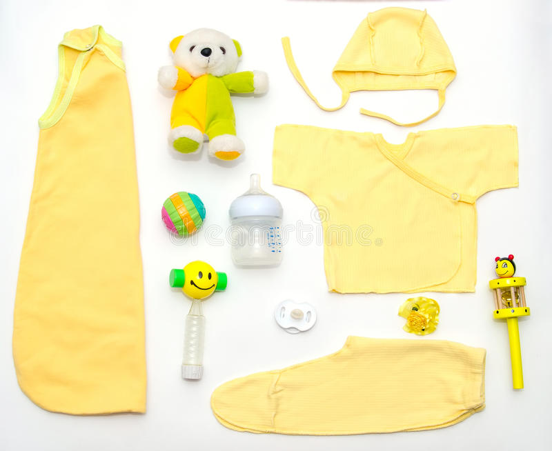 Top view of baby girl yellow clothes and toy stuff royalty free stock photos