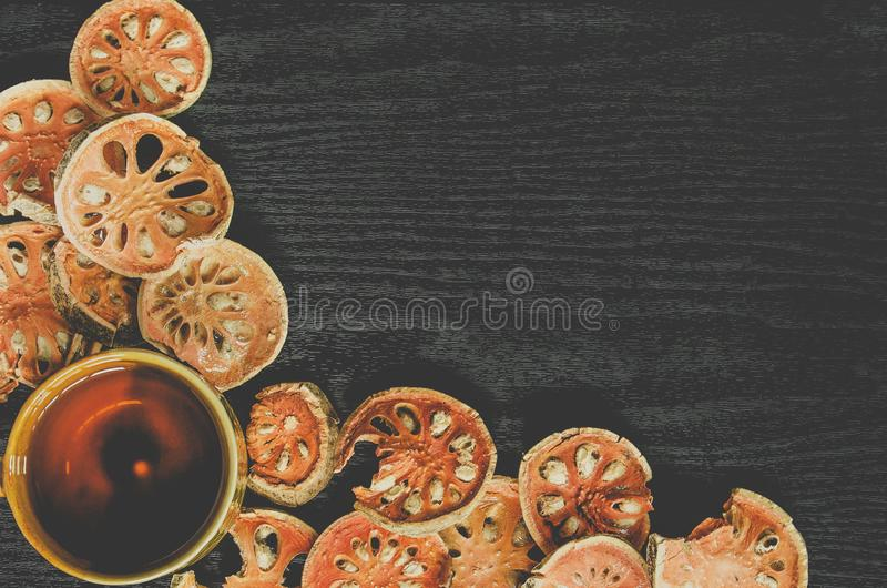 Top view of bael dry and glass tea and bael juice on the wooden floor stock photos