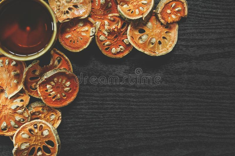 Top view of bael dry and glass tea and bael juice on the wooden floor stock image