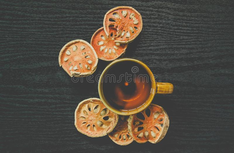 Top view of bael dry and glass tea and bael juice on the wooden floor royalty free stock image