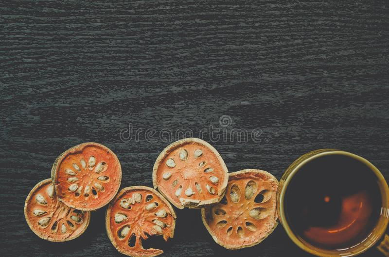 Top view of bael dry and glass tea and bael juice on the wooden floor stock photo