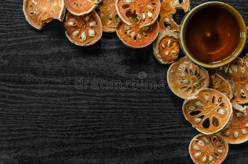 Top view of bael dry and glass tea and bael juice on the wooden floor royalty free stock photography
