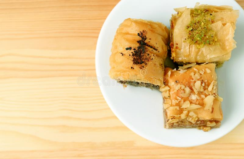 Top View of Baklava Pastries in Different Flavors Served on Wooden Table with Copy Space stock photo