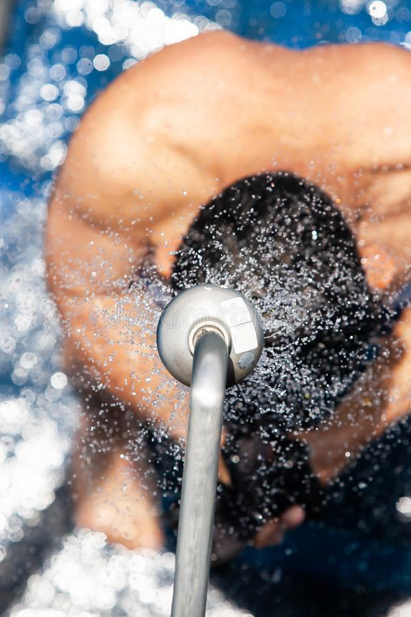 Top view of bare-chested man showering under refreshing freshwater on the cruise ship. Abstract transparent with bokeh on freshwater, bright sunny summer royalty free stock photos