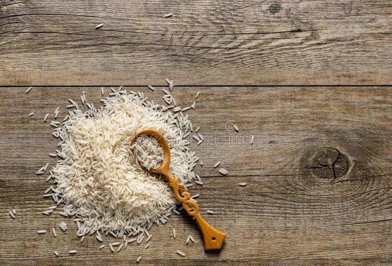 Top view of Basmati Rice pile with wooden spoon on the antique wooden background royalty free stock photos